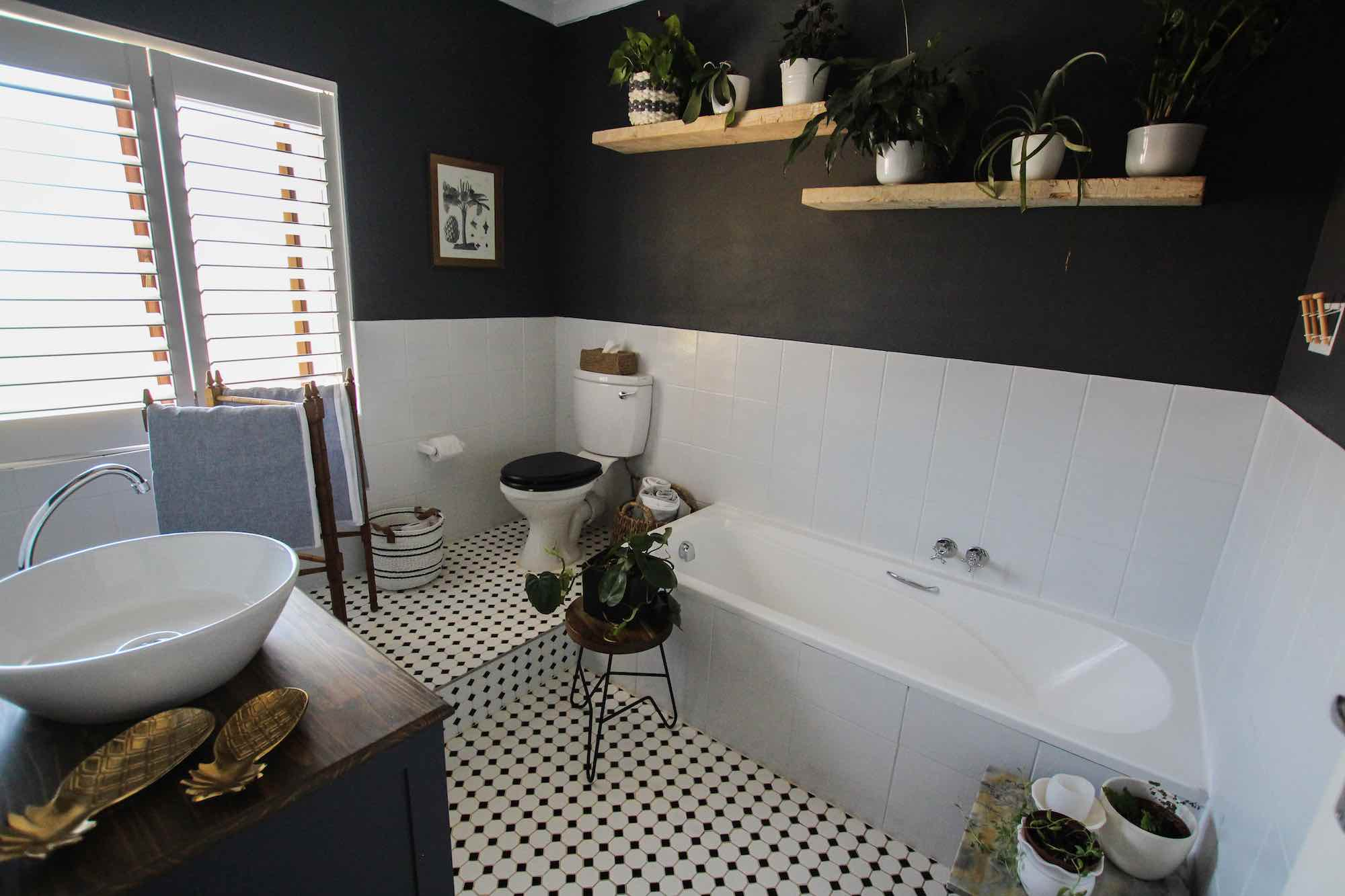 Bathroom decorated with indoor plants, wood furniture and decor accessories