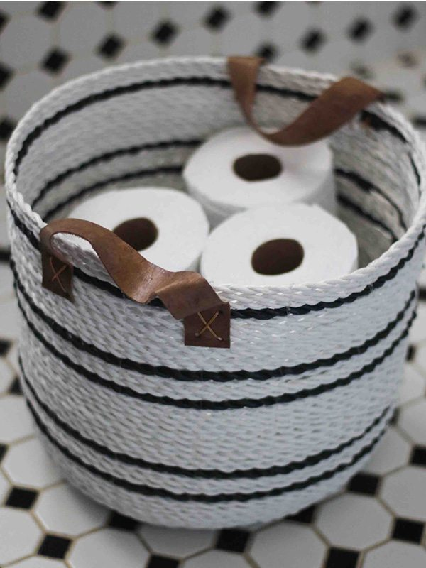 Black and white woven basket with leather straps for decoration and storage