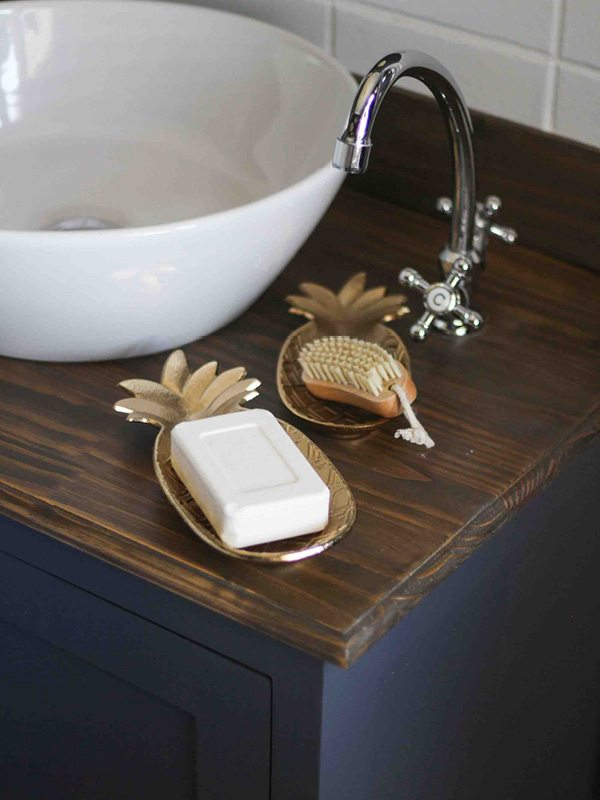Bathroom sink with wood top and gold accessories